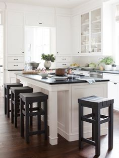 Dark-walnut floors, green soapstone counters, and custom stools bring weight to the kitchen's white cabinetry.