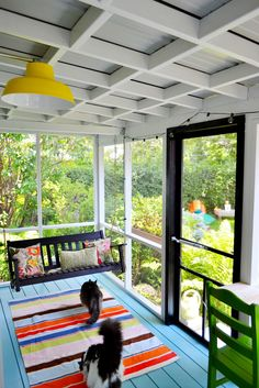 Screen porch. Colorful screened porch. Box beams. Blue floor. Yellow light. Black frame door.