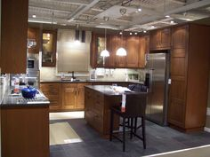 IKEA Lixtorp cabinets with slate tile floor, dark counters and off-white natural stone subway tile backsplash