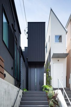 A skinny house clad in black steel by Apollo Architects & Associates slots into a tiny plot of land in Tokyo, Japan, and features minimalist interiors.