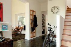 En el hall de acceso se hizo un espacio para la bici con protectores de madera y un bicicletero de hierro. En la pared opuesta, perchero de tres módulos en madera de paraíso ( Net)..