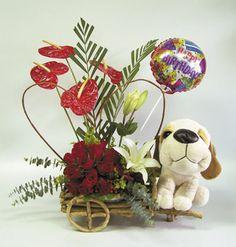 Delicado arreglo floral con una esfera de rosas, anturios, lirios acompañado de un globo,un peluche, en una base de mimbre en forma de carreta.