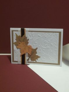 Fall greeting card  -ribbon / paper strips  -leaf punch out - chalked  -embossed panel with mounted on larger colored panel.  -cream colored card-stock and envelopes.
