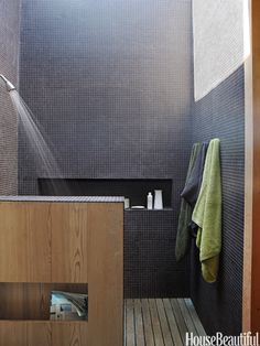 Bright Black Bath. In the master-bath shower of a modern New York beach house designed by architect Cary Tamarkin, the walls are clad in black porcelain tiles that soar up to a wall-to-wall skylight.