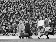 4th March 1972. The cleaners at White Hart Lane are heading off home, from work, seemingly oblivious to Tottenham's Roger Morgan and Manchester United full back Tommy O'Neill.