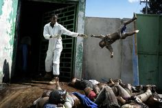 A man throws a dead body in the morgue of the general hospital in Port-au-Prince, Haiti, January 15, 2010, following the 7.0 magnitude earthquake on January 12