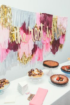 Love this table set-up with the pink and metallic fringe backdrop