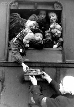 A staff of the National Socialist People's Welfare (NSV) gives food to mothers and children before their departure to their guest families in 'safe' areas, in February 1944.