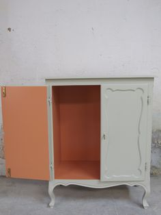 Ex-scarpiera portata a essere un semplice,essenziale e capiente mobile in stile rimodernizzato utilizzando due palette di colori.Finitura esterna grigio verdastro satinato,interno rosa salmone lucido. Re-issue