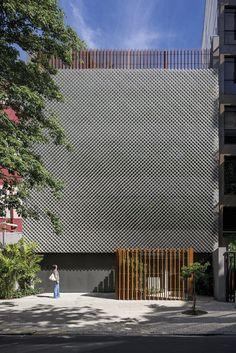 Prédios residenciais e lojas constituem a vizinhança do edifício Aníbal. Recoberta com chapas metálicas perfuradas, a face leste permite a entrada da luz natural sem comprometer a privacidade do ambiente de trabalho