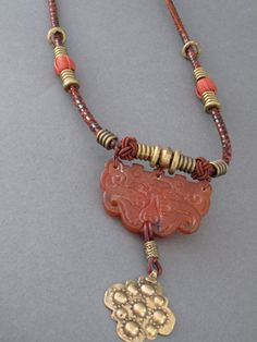 A carved  chinese jade  pendant with a hand hammered bronze drop on a decorative leather slip knotted cord set off with brass and silk beads