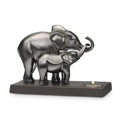 """A heartwarming moment between mother and baby is captured in glazed ceramic. The gray metallic finish reflects the shimmering glow of a tealight, sold separately. 6 1/4"""" h, 9"""" w.  Price:  $60.00 each"""