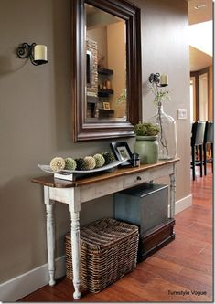 Smallish console table where barrister cases are now. Add a mirror over to magnify window light. Tray on top to corral keys and smalls. Table lamp for light in that corner. Basket or box below for storage (dog walking stuff, extra liv rm throw) OR tuck a small bench or ottoman beneath for an extra seat/spot to tie shoes, etc