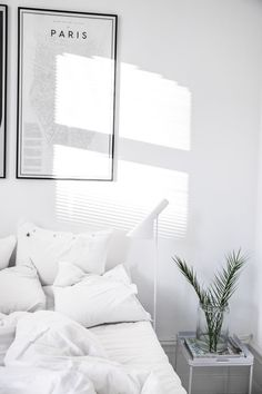 A beautiful fresh white bedroom featuring the Louis Poulsen AJ Floor Lamp.