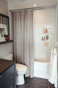 Lovely small bathroom - Dark tile floor, subway tile shower, love the shelf above toilet