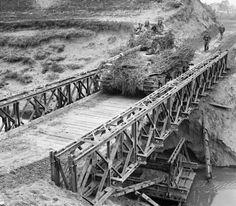 A heavily camouflaged Sherman tank crosses a Bailey bridge over the River Santerno near Imola, 12 April 1945