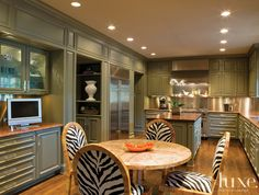 #Gray lacquered #cabinets stainless steel backsplash, with the #zebra #Duralee fabric on the #chairs adds a touch of flair... #Luxe