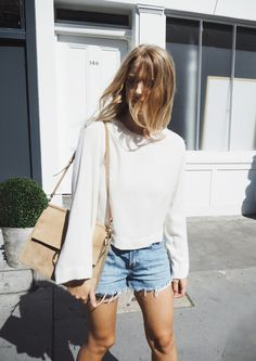 outfit idea: long sleeve crop top with vintage light wash levi denim cut off high waisted shorts and a chloe bag