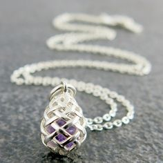 Weave Small Egg Pendant in Silver, with a piece of Amethyst rough gemstone inside.