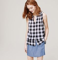 We adore the swingy sweet of this gingham cotton style. Jewel neck. Sleeveless. Button front. Banded neckline. Shirred beneath front and back yoke.