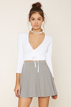 This knit crop top features a surplice front that wraps around and ties in back, a V-neckline, and long sleeves.