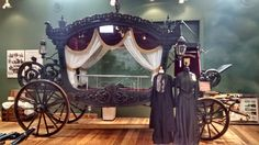 austrian hearse, 1900. this carriage would have been used for the funerals of the nobility, or the very rich. alongside the hearse are two gowns suited for mourning.