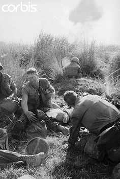 29 Dec 1967, Da Nang, South Vietnam --- A wounded U.S. Marine is given first aid as smoke from an exploding shell billows in the background after the Marines were ambushed by Viet Cong in a cemetery 20 miles south of here Dec. 28.