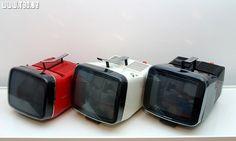 "Side by side, 3 Brionvega Algol TV  In red, the original : Brionvega ""Algol 11"" b/w TV, design by Marco Zanuso and Richard Sapper in 1964  In white, the evolution : Brionvega Algol TVC 11, re-design by Marco Zanuso in 1989, now a color TV  In black, a l MCA TVC Matrix"
