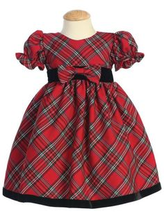 Red and black plaid holiday dress with round neckline and short puff sleeves. Black velvet waistband with plaid bow attached to long tie back sash. Plaid skirt with velvet trim at the bottom. Dress is