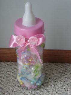 This adorable baby bottle bank is filled with 18 washcloths rolled to look like candies.  Each one is rolled in tulle and adorned with ribbons. The washcloths are pink yellow and white for the girl's bottle and blue, green and white for the boys bottle.  There is a bow with two rattles for decoration.  makes a great game at a baby shower- guess how many washcloths.