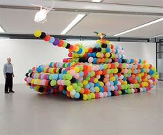 Inflatable tank made out of colorful balloons by German artist Hans Hemmert.  Balloon Tank sculpture encourages kids and adults to make art not war.