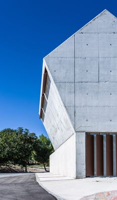 One end of this concrete funeral building in Spain by Salas Architecture + Design angles up towards the sky