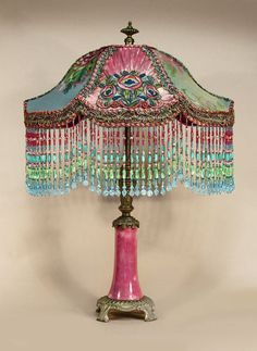 One-of-a-kind hand-beaded victorian lamp shades and fully restored antique table lamp. 'VADER' shaped shade is dyed hot pink and covered with metallic lace on most sides. The front, center panel is shirred, metallic-shot lame, overlaid with a silk embroidered floral appliqué. Heavy, silver and multi-colored trim is in the cuff. Hand beaded fringe around the bottom edge. This sits on a beautiful, bronze and pink porcelain table lamp.