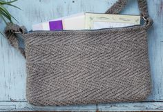 FREE PATTERN: Talitha Kuomi dreamed up this  design, the Tasa bag. The chevron slip stitch pattern creates a sturdy fabric with a woven appearance and the slightly marled yarn adds depth to the stitch without diminishing the texture. Little finishing details, from the zipper to the strap with tabs and rings, give Tasa a polished look.