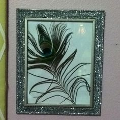 DIY: Plain picture frame with silver pipe cleaners around the boarder, and a peacock feather inside the frame. (: