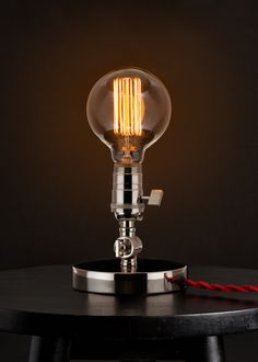The Sixth Ward Edison Lamp is handmade in Texas, using American-sourced machined parts. It features a removable raw steel parabolic shade, a sturdy 2 lb. base, and an adjustable joint, allowing the lamp to be pivoted forward and back.