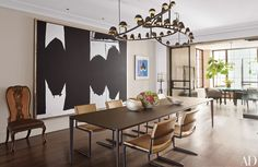 A custom-made Frederik Molenschot light fixture from Carpenters Workshop Gallery presides over the dining room, which features artwork by Robert Motherwell (left) and Richard Diebenkorn. The Holly Hunt Studio dining chairs, covered in a Great Plains leather, are pulled up to a matching table. The chair at left is by Rose Tarlow Melrose House, the floor lamp is by Alison Berger Glassworks, and the silver bowls are by Alexandra Agudelo.