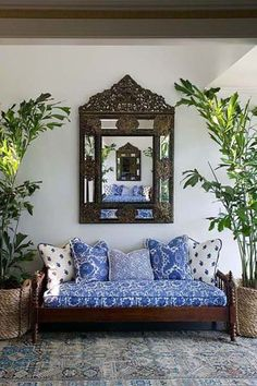 nice mix of blue and white fabrics, love the large mirror and palms in baskets