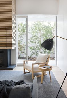 Alfred Street Residence by Studio Four | Remodelista A slatted wood chimney wall rises above a black steel hearth. The architects say they tied together the room by introducing a series of horizontal and vertical elements. The side table is the Around Table by Muuto.