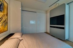 Modern Compact Bedroom Design With Grey Striped Duvet Cover And White Gloss Sliding Door Also Wall Mounted Tv Cabinet Curved Corners And Wood Floor: Modern Chic Apartment with Playful Interiors In Tel Aviv