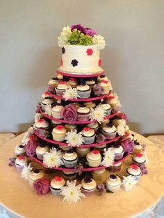 Bright pinks and purples along with fresh flowers accentuate this cupcake tree. www.mitchels.ca #wedding #weddingcakes #flowers #cupcakes