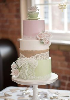 Hessian and lace wedding cake, teacup topper in green and pink theme.