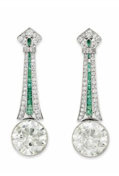 A PAIR OF DIAMOND AND EMERALD EAR PENDANTS. Each suspending a bezel-set old European-cut diamond, weighing approximately 7.18 and 6.72 carats, to the circular and single-cut diamond tapered plaque surmount, trimmed with calibré-cut emeralds, mounted in platinum.