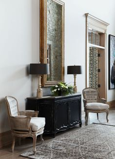 Simply elegant. I love this foyer. The clean lamps next to the printed canvas chair backs. And especially being able to see the stone wall in the mirror.