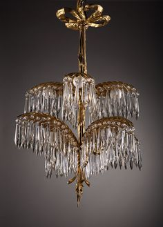 gilt bronze chandelier with eight palm tree branches on two ornate levels with crystal drops.
