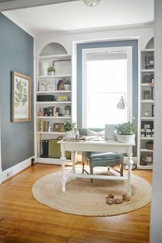 Navy Blue Office - with floor to ceiling bookshelves, round rug, & a desk in the middle of the room.