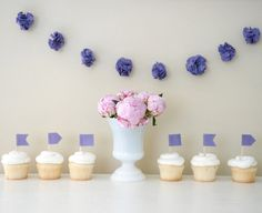 make small pom garland from tulle for doorway, mixed with matted pictures