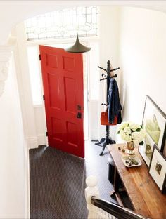 I like this idea...using a classic black penny round porcelain mosaic tile on a foyer floor. The contrast with the white walls and red door really work in this entry way. I assume an unglazed porcelain would work best on the floor...no slipping and sliding!  Like, like, like.