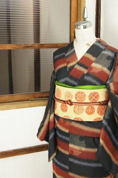 ブラウン、ベージュ、チャコールブラック、グレーのモダンでシックなカラーで織り出された大胆横ボーダーに、淡雪を重ねたような繊細な雪輪模様が浮かび上がる正絹紬の袷着物です。