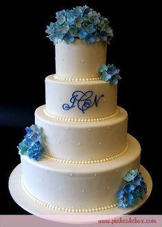 Bright blue hydrangea fondant flowers on a white wedding cake.